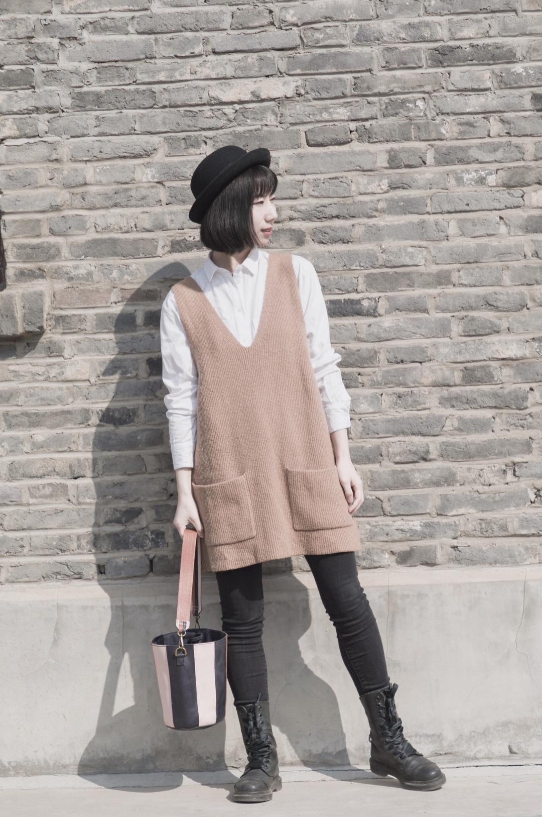 #打底才是一身穿搭的精髓啊!#  毛衣裙的减龄穿搭: 春天就是叠穿最好看的季节啦~白衬衫叠穿毛衣背心裙,内搭了基础款的slim牛仔裤。为了平衡感,搭了比较帅的马丁靴和窄沿帽。 整体色调是黑白驼色,水桶包色系与驼色呼应~